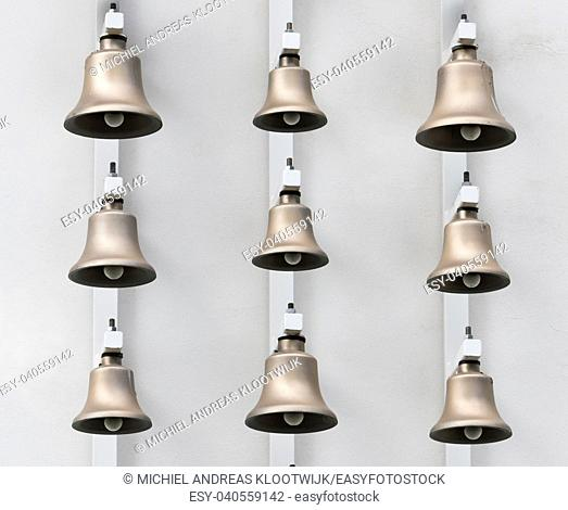 Modern bronze bells on background of white wall