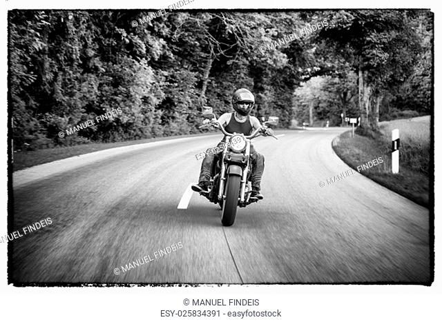 Tough guy with sparrow beard, undercut and blue jeans in motion on the road on a chopper bike