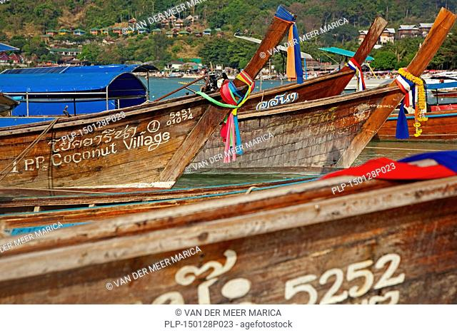 Prows of traditional wooden fishing boats on beach of one of the Ko Phi Phi islands, Southern Thailand