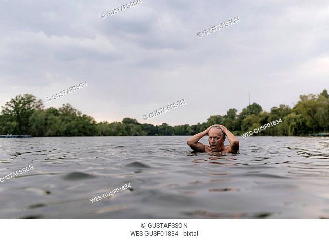 Senior man swimming in a lake