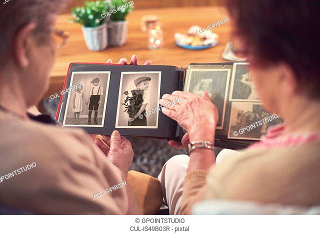 Over shoulder view of two senior women looking at old photograph album
