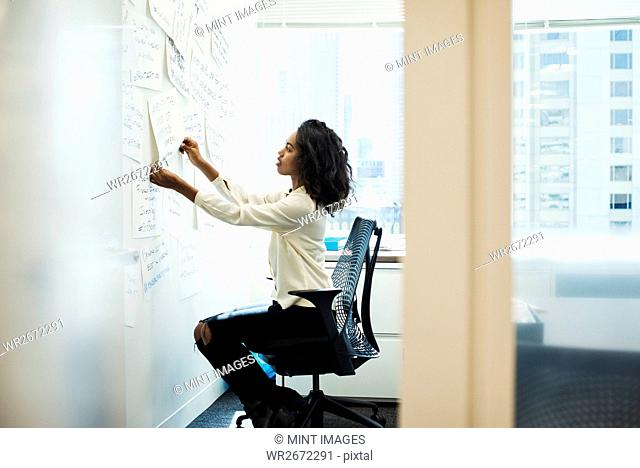A woman sitting on a chair in an office arranging pieces of paper pinned on a whiteboard