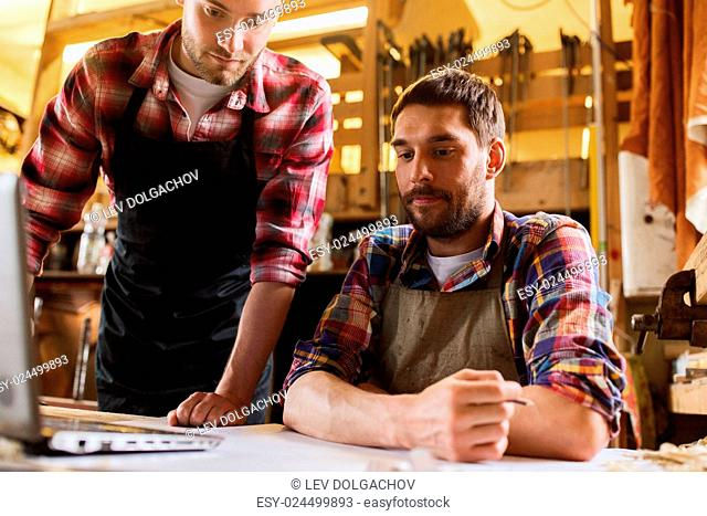 profession, carpentry, technology and people concept - two carpenters with laptop computer and blueprint at workshop