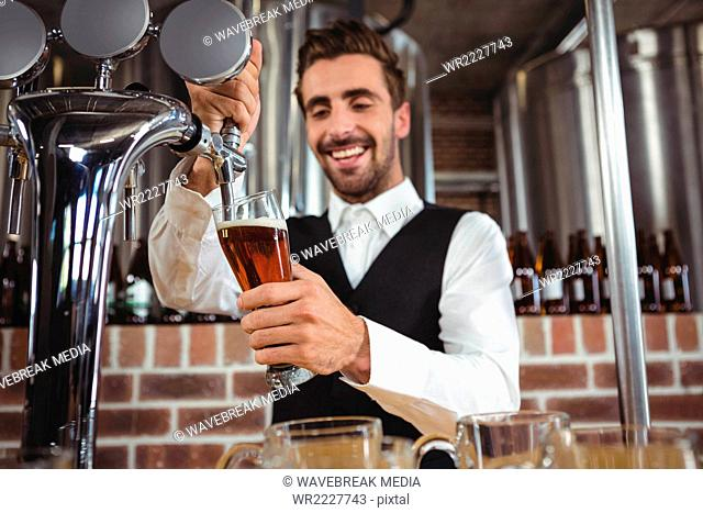 Handsome barman pouring beer
