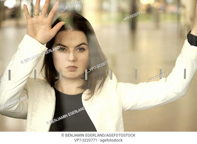 portrait of a woman indoors behind glass window, confident determined emotion, city life, in Munich, Germany