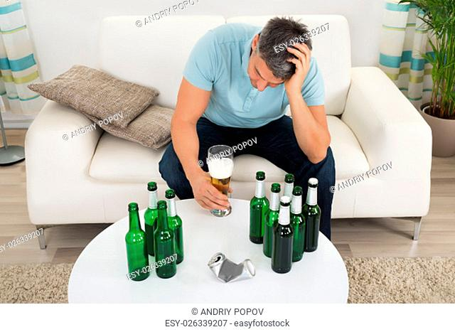 Mature Man Sitting On Sofa In Front Of Bottle Of Beer On Table
