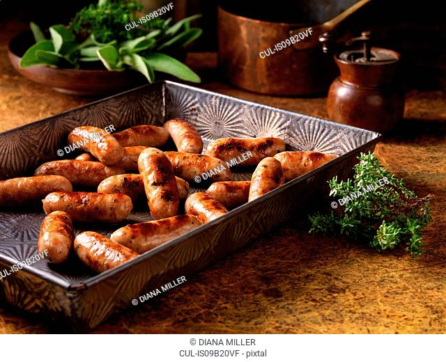 Christmas, celebration food, classic cocktail sausage selection, in baking tray, fresh thyme and sage