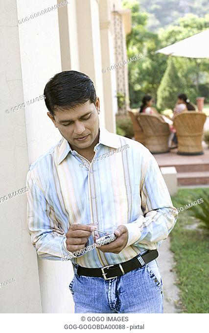 Man using an electronic organizer outdoors