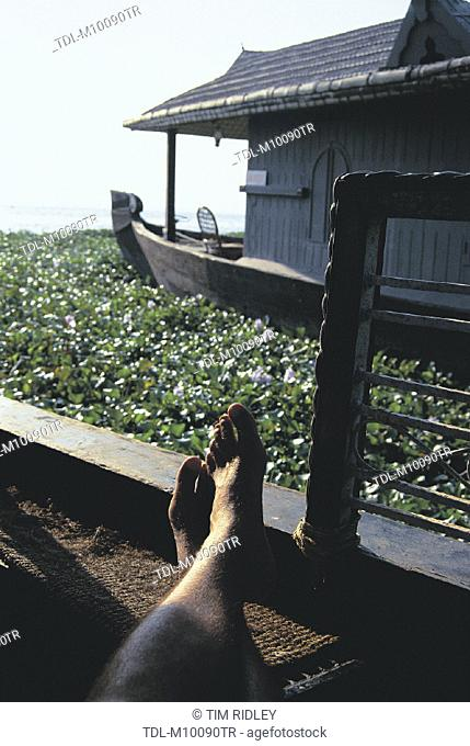 Feet, a man relaxing on a house boat, Lake Vembanad, Kerala, India