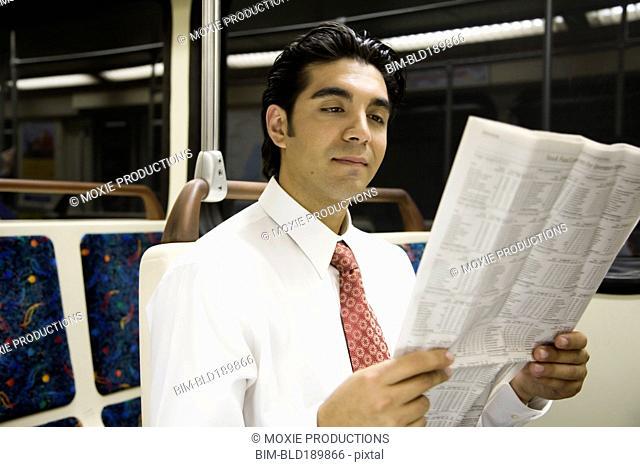 Hispanic businessman reading newspaper on subway
