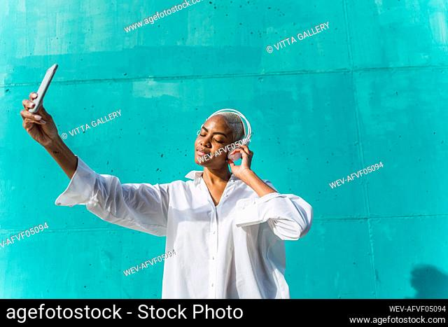 Beautiful woman standing in front of teal wall, listening music, taking selfies