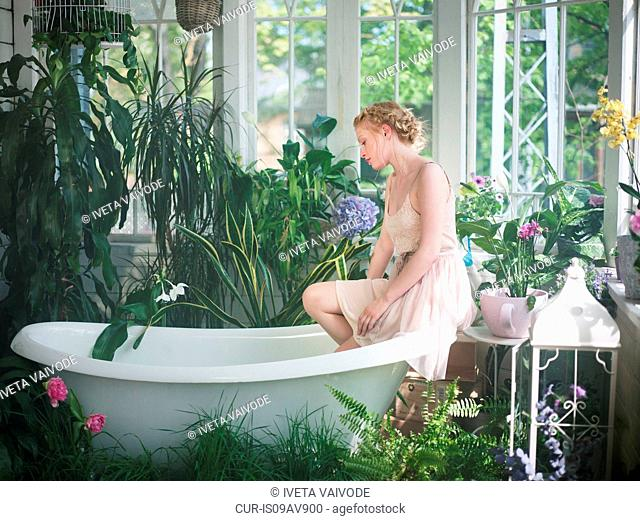 Young woman, sitting on edge of bathtub, in bathroom filled with plants