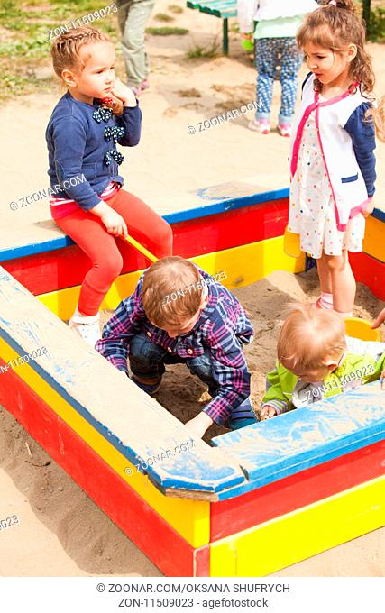 Children are playing at the playground with sand in the sandbox