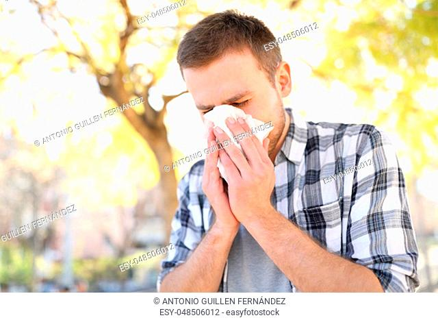 Allergic man sneezing covering nose with wipe in a park in spring season
