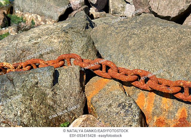 iron rusty ship chain in the midst of stones, summer day