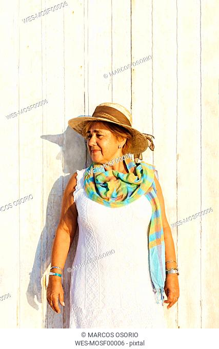 Portrait of a senior woman with a hat at a wooden wall