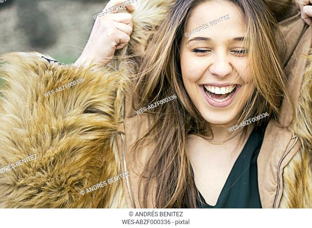 Portrait of laughing woman putting hood of a fur jacket on