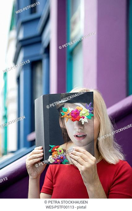 Woman covering face with book, reading poetry