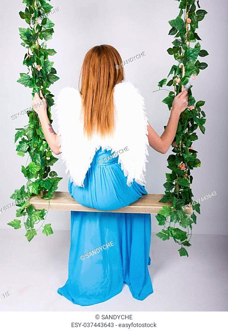 Beautiful young leggy redhaired woman in a long blue dress on a swing, wooden swing suspended from a rope hemp, rope wrapped vine and ivy