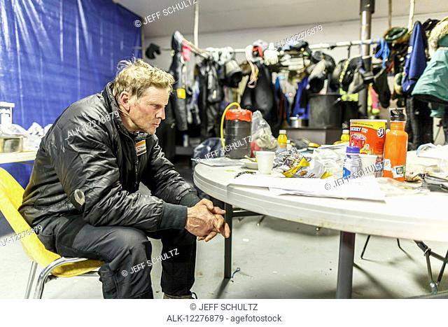 Lachlan Clarke has the 1, 000 mile stare as he rests in the community center as musher gear dries in the backgroud at the Tanana checkpoint during Iditarod 2015