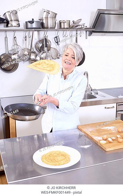 Mature woman in kitchen throwing up pancake in pan