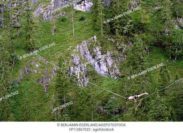 young athlete training on slackline over valley in nature, in south of Germany, Bavaria, near border to Austria