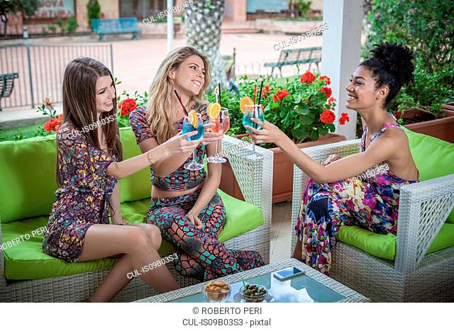 Three young women relaxing on apartment patio raising a cocktail toast, Costa Rei, Sardinia, Italy