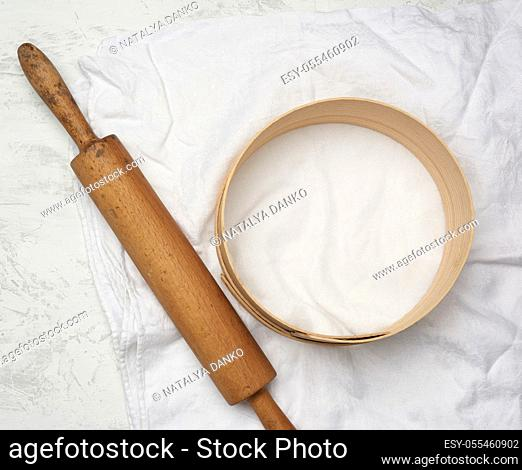 vintage wooden rolling pin and a round sieve lie on a white linen napkin, top view