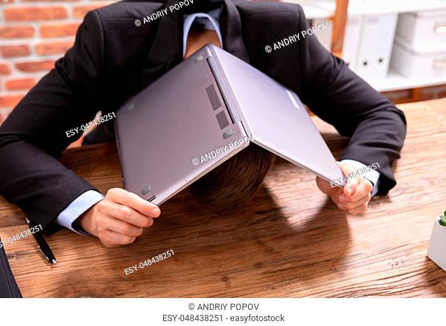 A Businessman Covering His Head With Laptop Over The Desk At Workplace