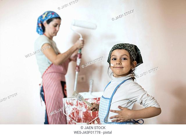 Portrait of little girl painting wall in children's room with her mother