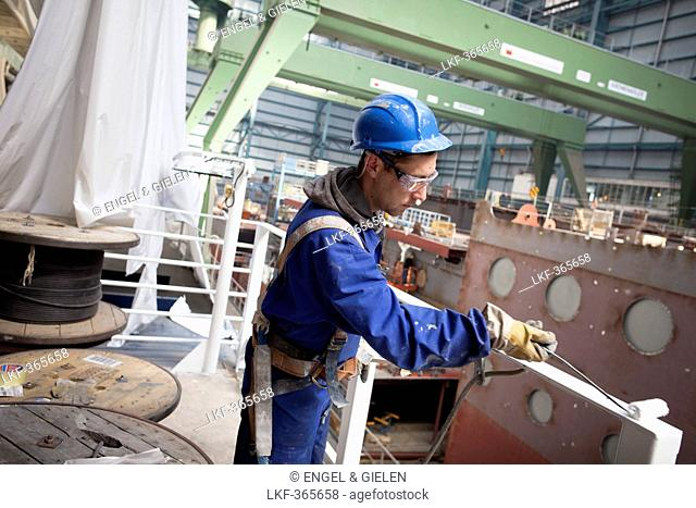 Worker painting railing, cruiser under construction in dry dock, Meyer Werft, Papenburg, Lower Saxony, Germany