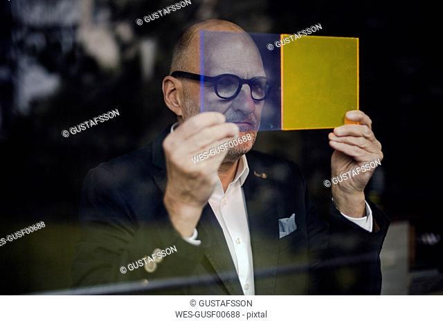 Senior architect standing at window, choosing materials