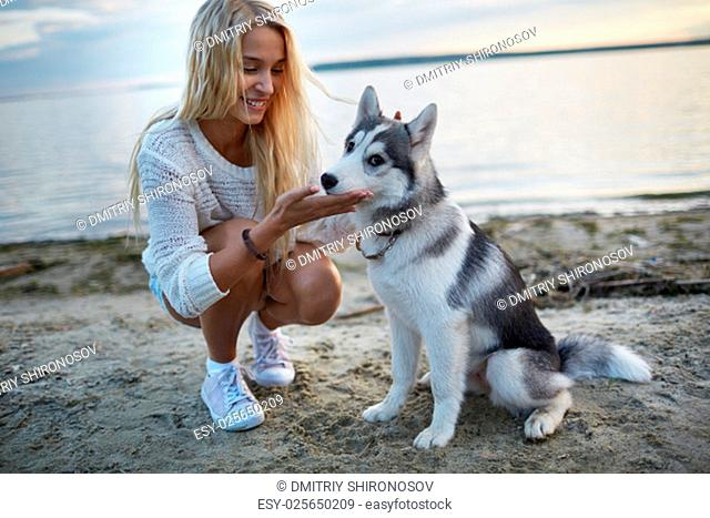 Pretty girl spending summer vacation by the seaside with her dog