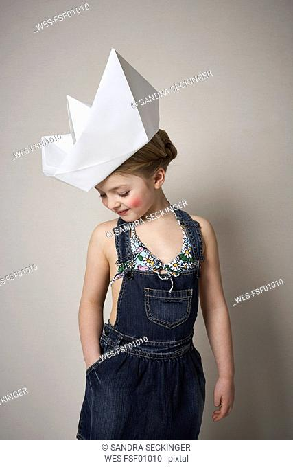 Little girl wearing big paper boat