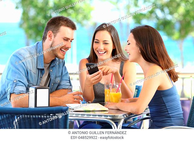 Group of three tourists searching gps locations on a smart phone sitting in a bar terrace on the beach during summer vacations