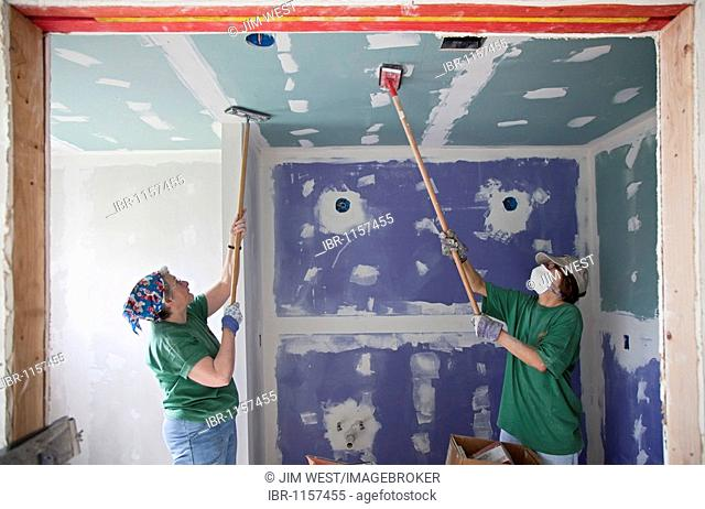 Jillian Robinson, left, and Patty Sanders, volunteers from the Marin Interfaith Council in California, repair a house damaged by Hurricane Katrina, Gretna