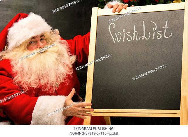 Santa Claus sitting near chalkboard with wishlist sign and blank copy space for checkboxes and your text