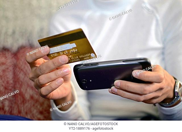 Young woman using online payment systems and banking, holding mobile telephone and credit card