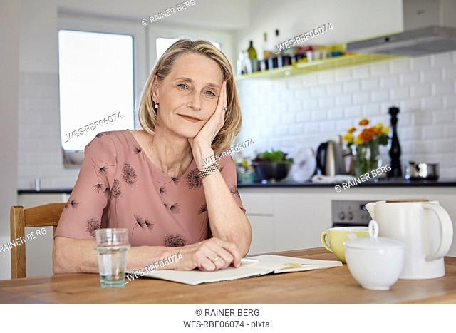Portrait of mature woman with notebook at kitchen table