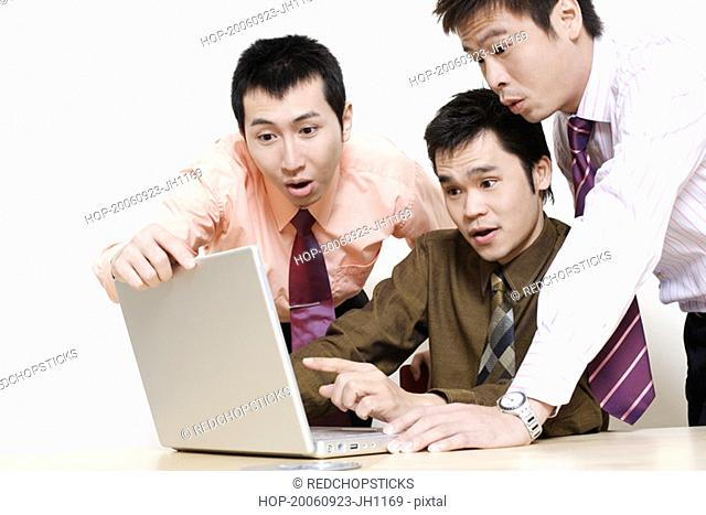 Three businessmen using a laptop and looking surprise