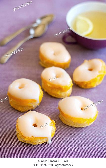 Glorias (puff pastry tartlets, Portugal) with lemon tea on a purple surface