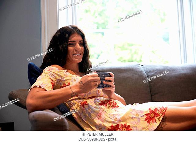 Woman with coffee mug on sofa