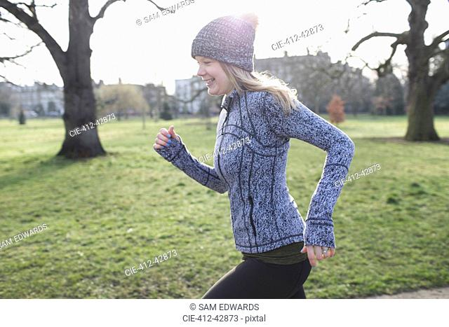 Smiling female runner running in sunny park