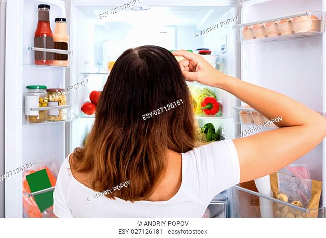 Rear View Of Confused Woman Searching For Food In The Fridge