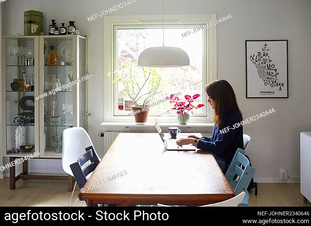 Woman working on laptop in living room