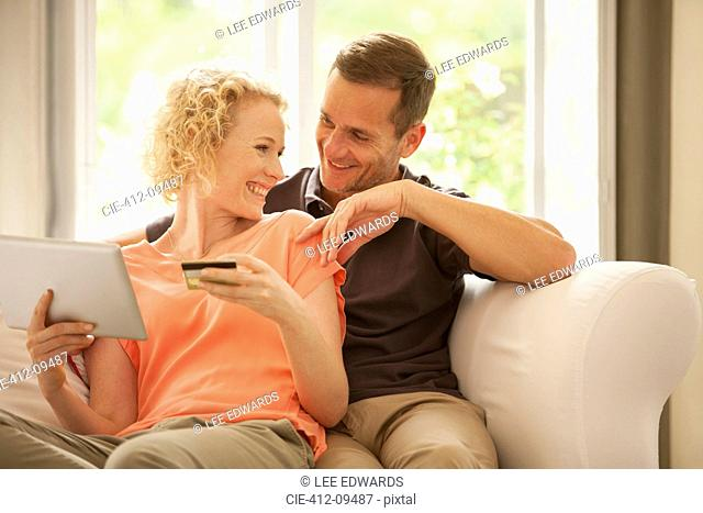 Couple shopping online on sofa