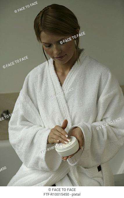 A woman holding a box full of white cream