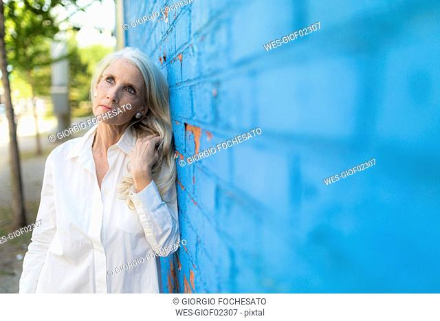 Portrait of daydreaming mature woman leaning against light blue wall