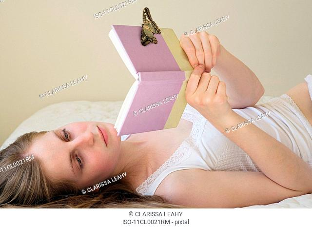 butterfly resting on teenage girls book