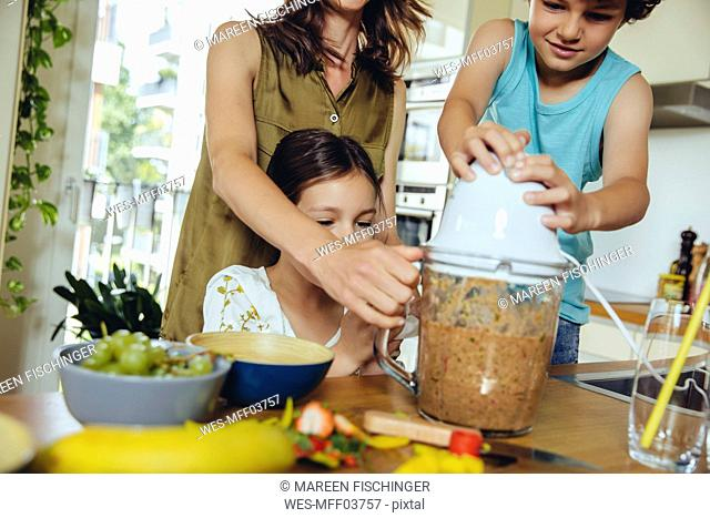 Mother and children blending fruit for a smoothie